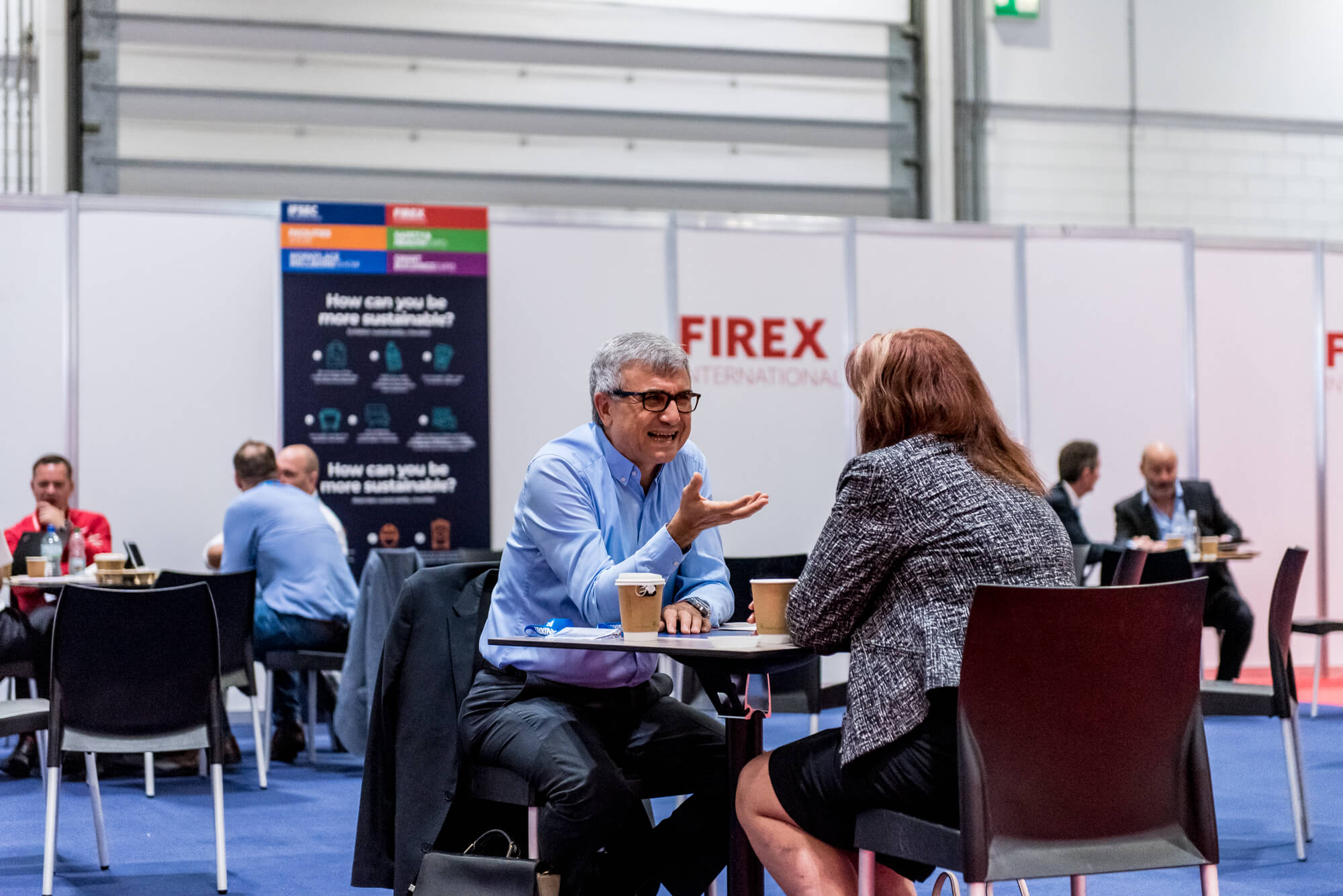 Two individuals talking at a coffee table at FIREX 2019